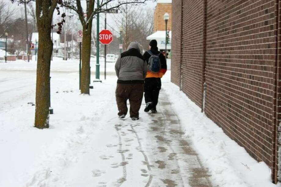 Two unidentified men are pictured walking along a snowy street in Big Rapids Tuesday. (Pioneer photo/Tim Rath)