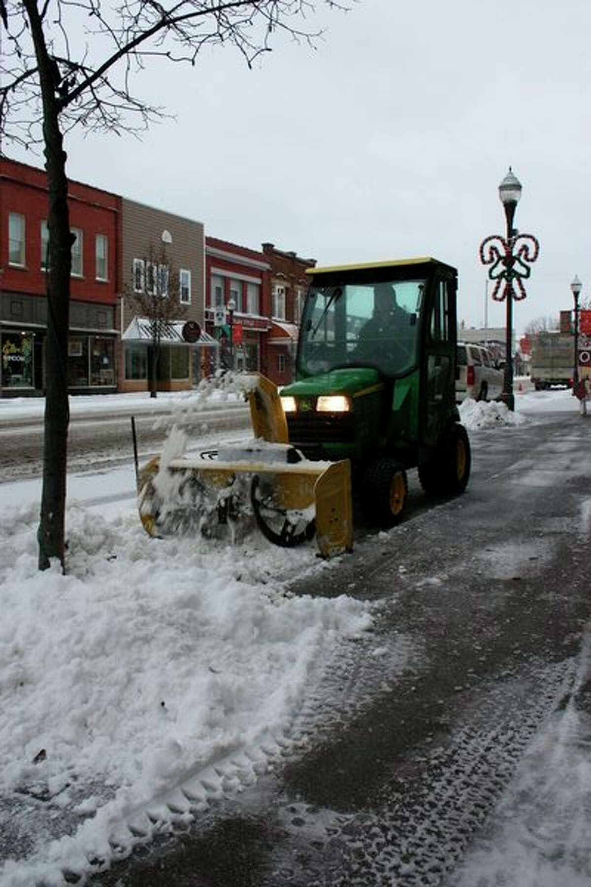 A small plow pushes snow out of the way on a sidewalk in Big Rapids on Tuesday. (Pioneer photo/Tim Rath)