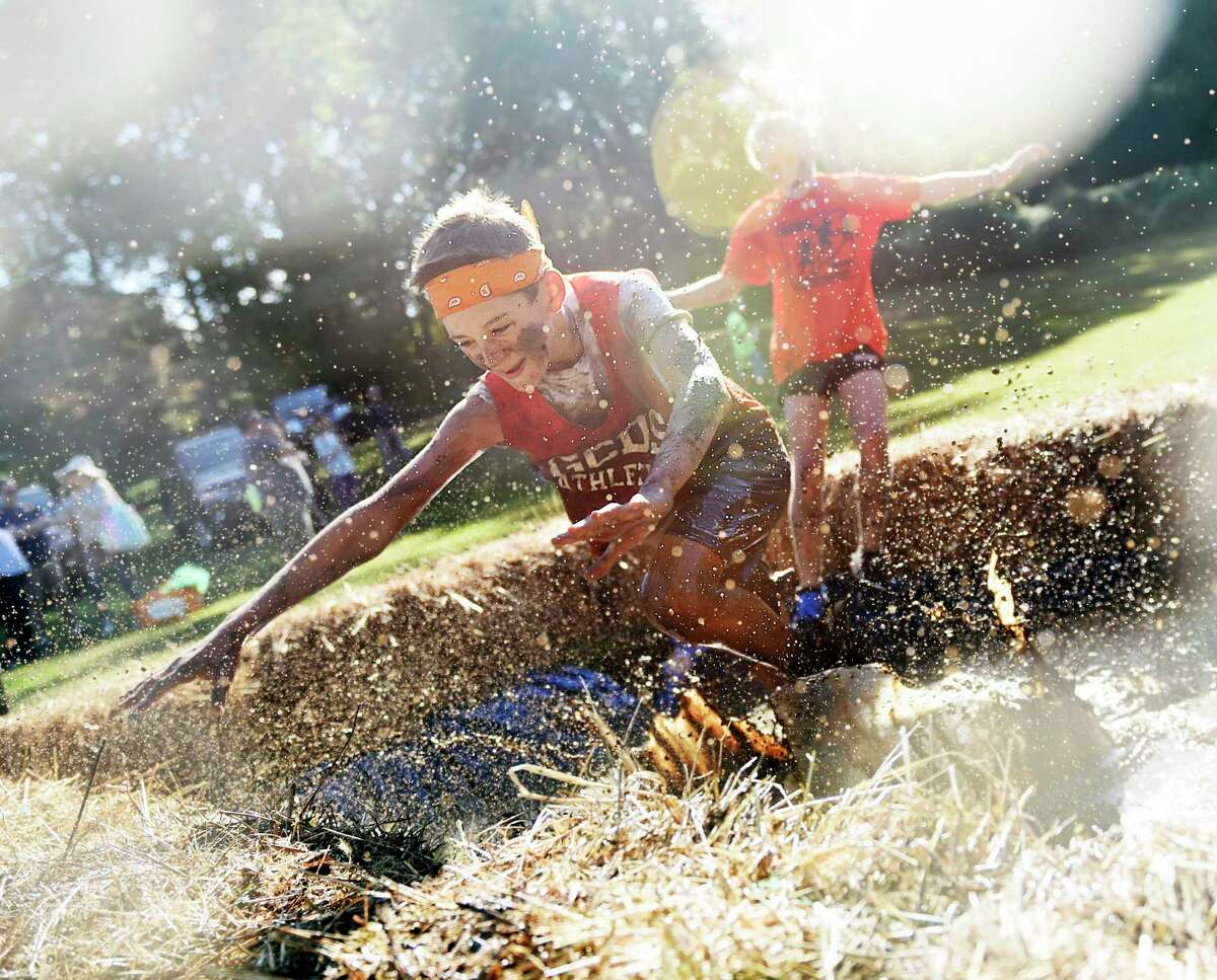 Greenwich's Zach Rohdie, 12, splashes in the mud pit near the finish line of the 8th annual Muddy Up 5K Run and Family Walk at Camp Simmons in Greenwich, Conn. Sunday, Sept. 29, 2019. Hundreds of participants ran through the course full of manmade obstacles including several mud pits. Proceeds from the event benefited the Boys & Girls Club of Greenwich.