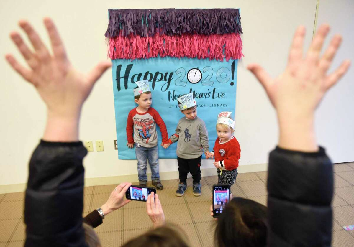 Stamford children Martin Dragan, left, 4, Alexander Boguski, center, 3, and Sara Dragan, 2, pose in front of New Year's backdrop as their parents take photos and a librarian attempts to get their attention during the Noon Year's Eve Party at Ferguson Library. The children's event celebrated the New Year by counting down to noon with music, dancing, crafting 2020 crowns, puzzles, and a New Year's photo backdrop.