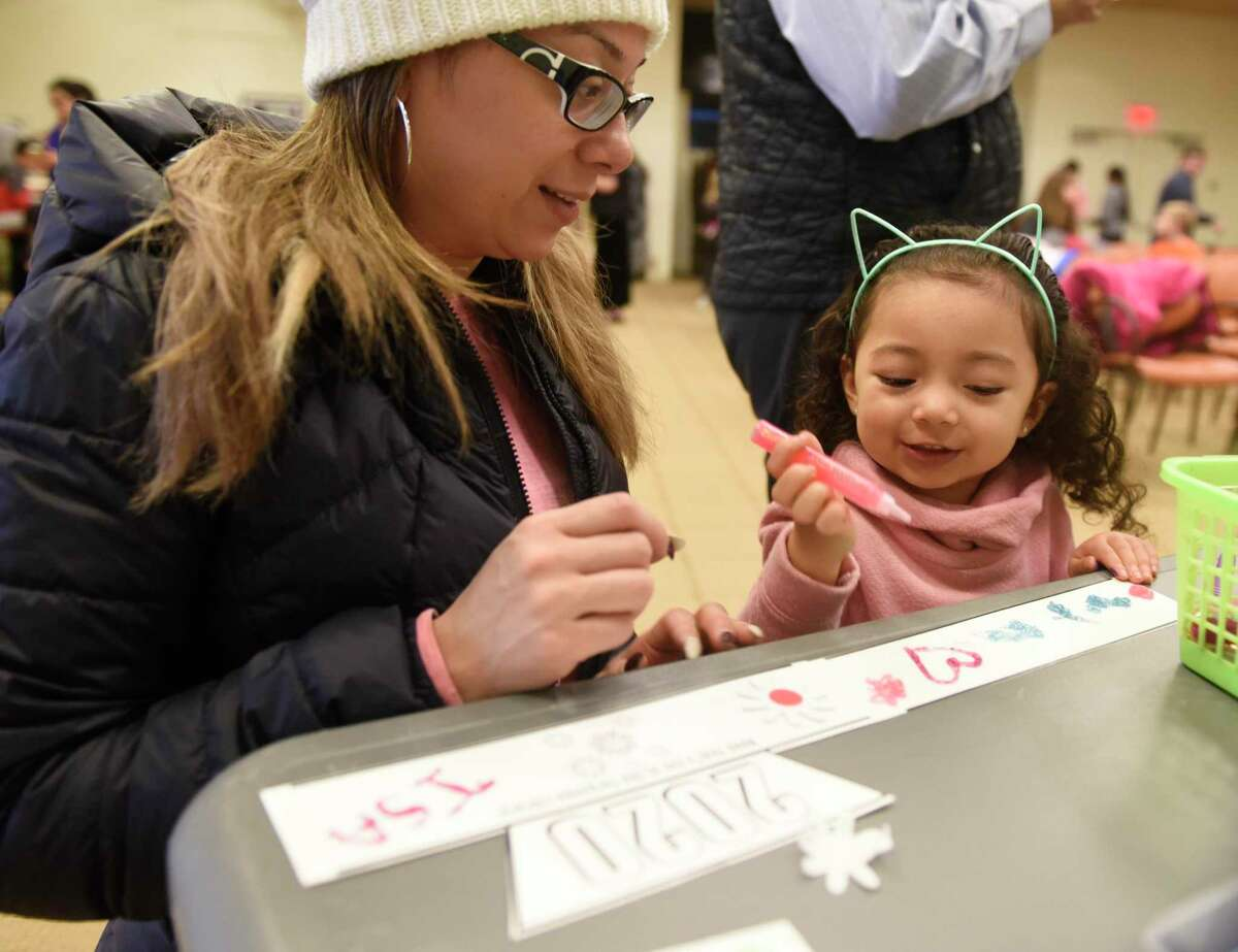 Stamford's Kenia Flores and her daughter, Isabelle Flores, 3, create a New Year's crown during the Noon Year's Eve Party at Ferguson Library. The children's event celebrated the New Year by counting down to noon with music, dancing, crafting 2020 crowns, puzzles, and a New Year's photo backdrop.