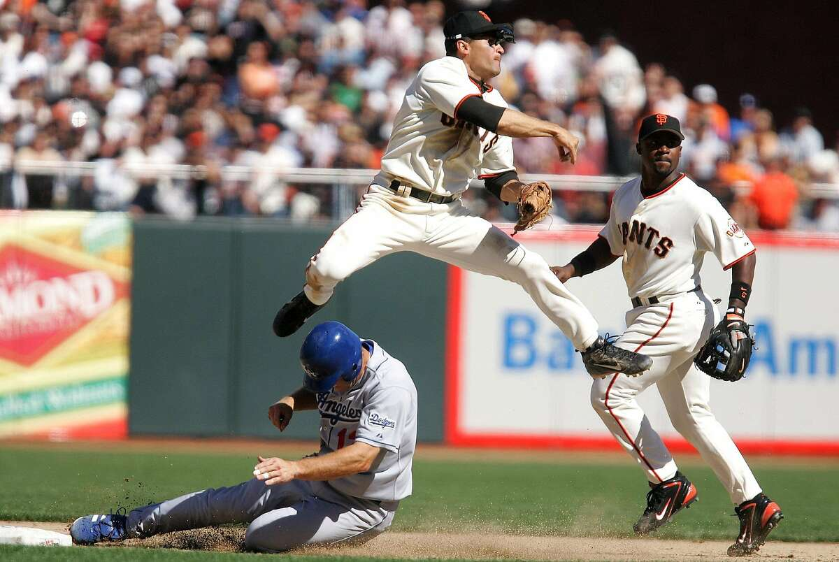 Los Angeles Dodgers' Jeff Kent, bottom, is forced out at second as San Francisco Giants shortstop Omar Vitzquel turns a double play in the ninth inning in San Francisco on Tuesday, April 5, 2005. The Giants won 4-2. Giants second baseman Ray Durham watches. (AP Photo/Jeff Chiu)