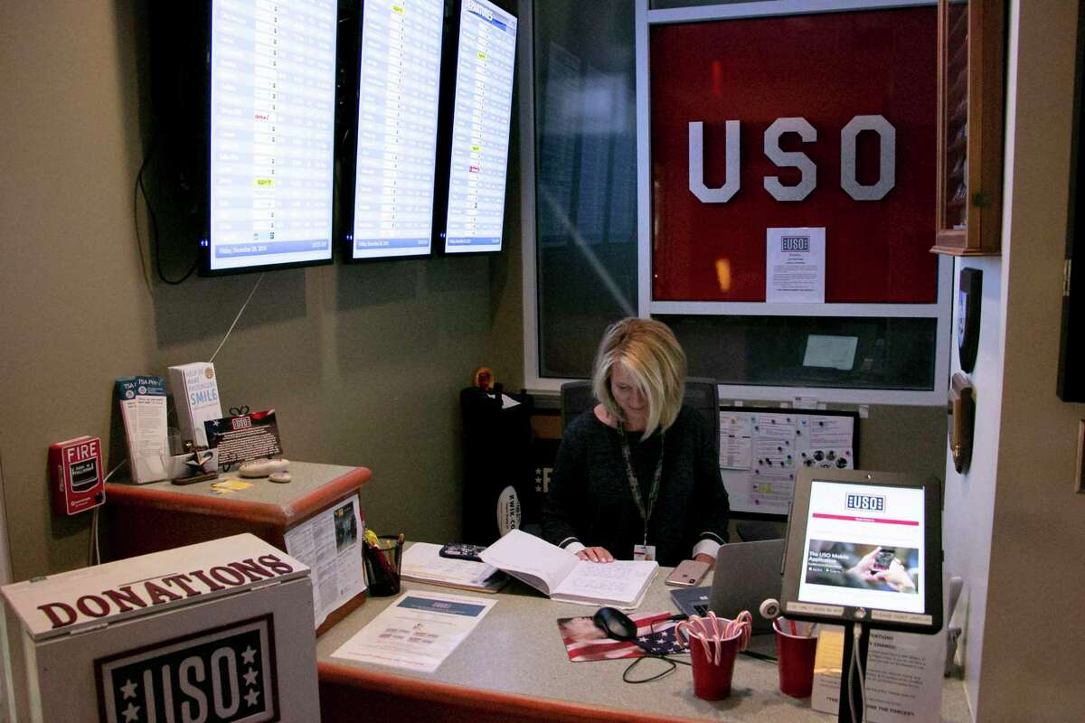 Jeanne Cantas, a new volunteer to the USO, sits at the entrance desk reading. This is where active or retired military and their families check in to show their ID badge.