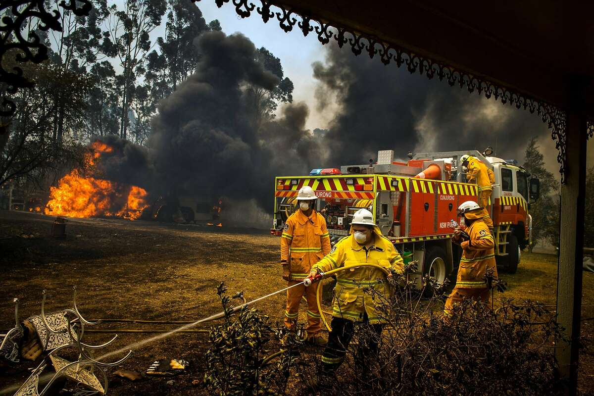 Firefighters protect a house in Conjola, Australia, on Tuesday, Dec. 31, 2019. The country's east coast is dotted with apocalyptic scenes on the last day of the warmest decade on record in Australia.