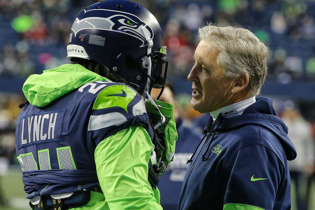 Head coach Pete Carroll talks with Seattle Seahawks running back Marshawn Lynch (24) onfield before his first game back with the Seahawks in four years. (Genna Martin, Seattlepi.com)