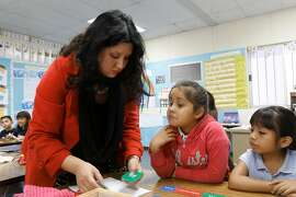 In this file photo from 2014, Letisia Huertado is helping students Destiny Valle and Ashley Vargas construct sentences in their first grade class at Parkview School in El Monte. California is home to more than 175,000 newcomer immigrant students, but author Sam Finn argues that the state isn't collecting enough data on their demographics or outcomes.