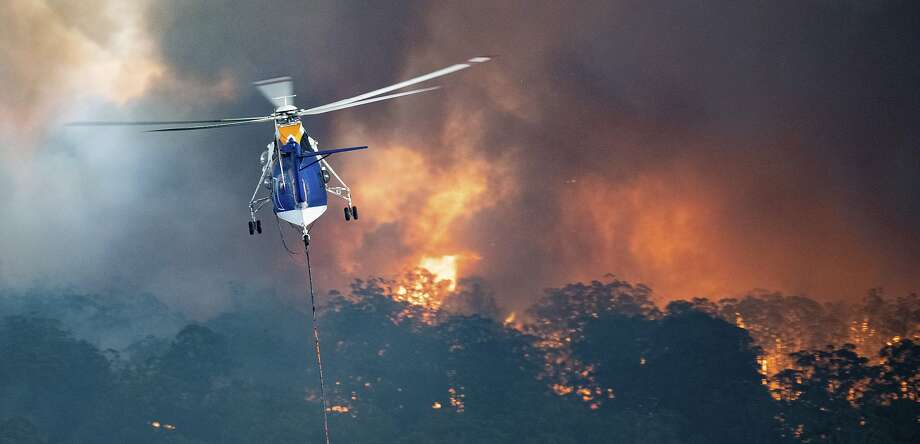 A helicopter tackles a wildfire in East Gippsland, Victoria state. Fires burning across the nation's two most-populous states trapped have killed 12 and destroyed more than 1,000 homes. Photo: State Government Of Victoria