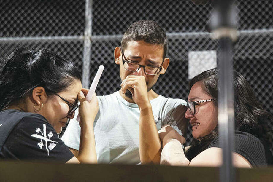 Three Walmart workers — Melisa Gonzalez, Jesus Romero and Raven Ramos — who helped people to escape during a mass shooting in August cry during during a vigil at Ponder Park in honor of the shooting victims in El Paso, Texas. Photo: Lola Gomez | Austin American-Statesman (AP)
