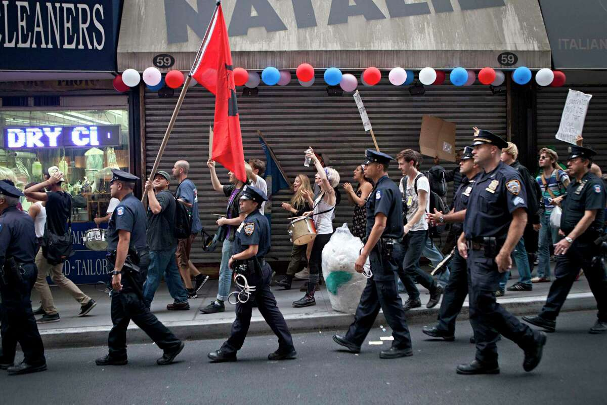 """FILE PHOTO - New York City police officers monitor protesters affiliated with the """"Occupy Wall Street"""" protests as they march through the Financial District in New York, on Monday, Oct. 10, 2011. (AP Photo/Andrew Burton)"""