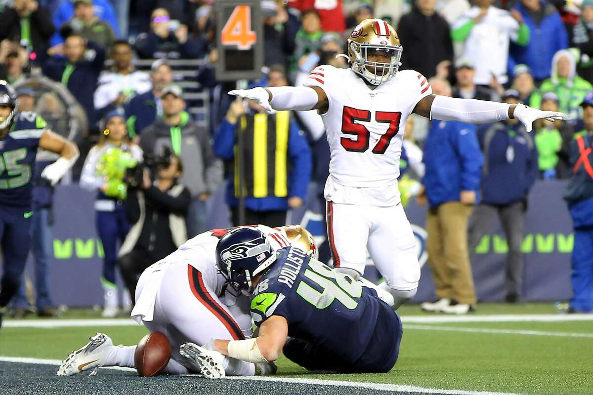 San Francisco 49ers linebacker Dre Greenlaw (57) signals no touchdown as Seattle Seahawks tight end Jacob Hollister (48) lands inches short of the goal line after a four yard pass on fourth down at the end of the fourth quarter of Seattle's game against San Francisco, Sunday, Dec. 29, 2019 at CenturyLink Field.