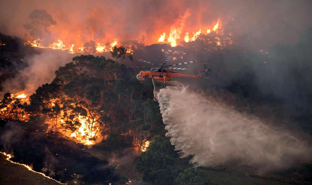 A photo provided by the State Government of Victoria, Australia, shows a helicopter dumping water on a wildfire near Bairnsdale on Tuesday, Dec. 31, 2019. The country's east coast is dotted with apocalyptic scenes on the last day of the warmest decade on record in Australia.