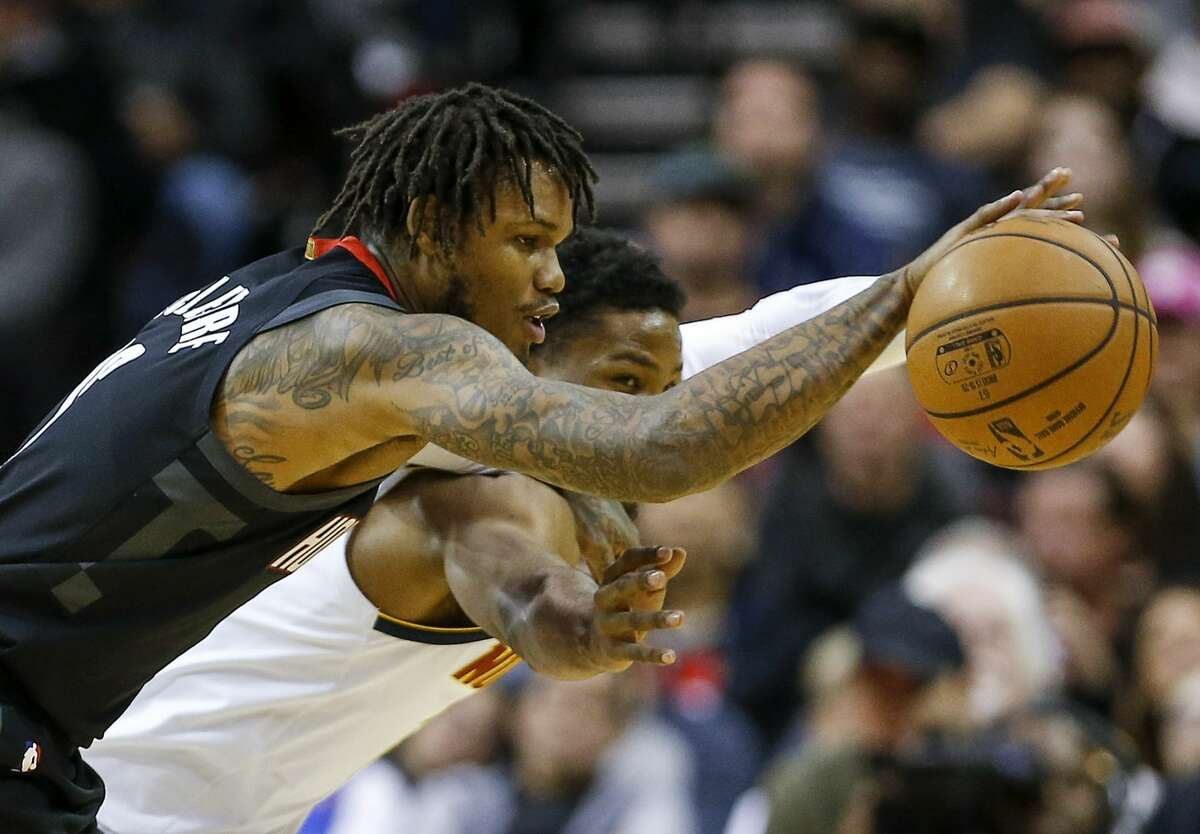 Houston Rockets guard Ben McLemore (16) and Denver Nuggets guard Malik Beasley (25) go after the ball during the third quarter of an NBA game at the Toyota Center on Tuesday, Dec. 31, 2019, in Houston.