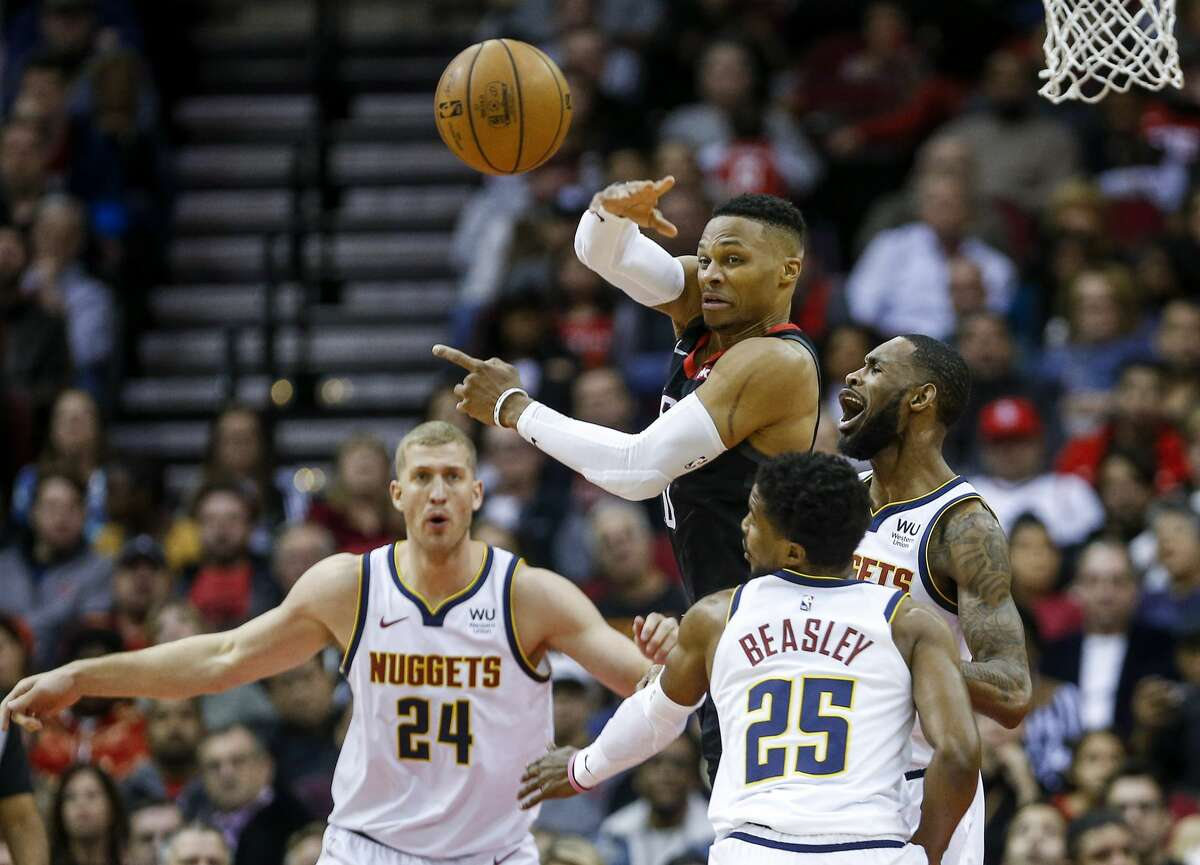 Houston Rockets guard Russell Westbrook (0) passes while under pressure from Denver Nuggets guard Malik Beasley (25), guard Will Barton (5) as Denver Nuggets forward Mason Plumlee (24) looks on during the third quarter of an NBA game at the Toyota Center on Tuesday, Dec. 31, 2019, in Houston.