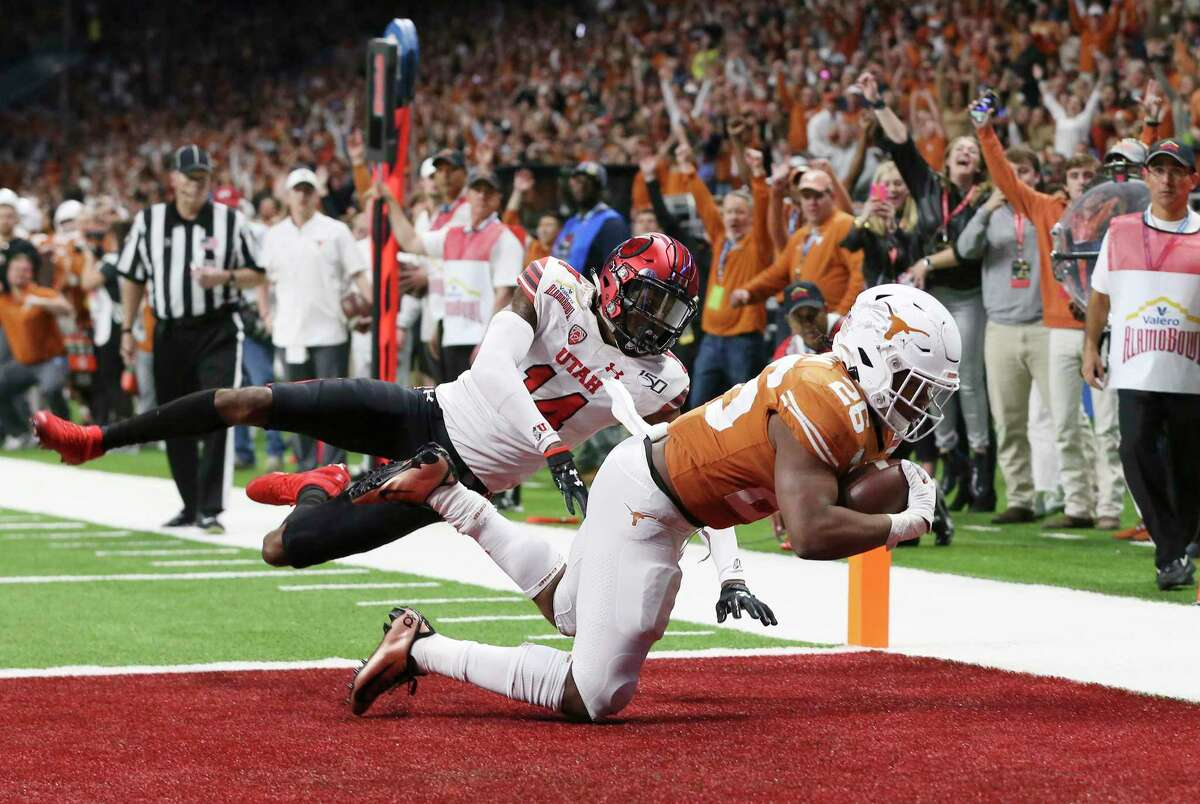 Texas Longhorns' Keaontay Ingram (26) scores a touchdown against Utah Utes' Josh Nurse (14) in the third quarter at the 2019 Valero Alamobowl at the Alamodome on Tuesday, Dec. 31, 2019.
