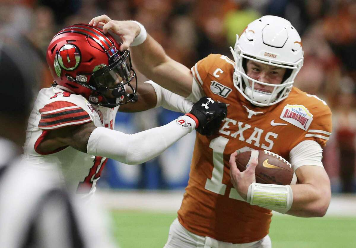 Texas Longhorns' quarterback Sam Ehlinger (11) fights off a tackle from Utah Utes' Josh Nurse (14) in the third quarter at the 2019 Valero Alamobowl at the Alamodome on Tuesday, Dec. 31, 2019.