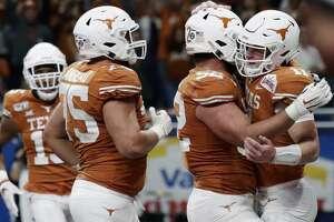 Texas quarterback Sam Ehlinger (11) celebrates his touchdown run against Utah with teammates during the second half of the Alamo Bowl NCAA college football game in San Antonio, Tuesday, Dec. 31, 2019. (AP Photo/Eric Gay)