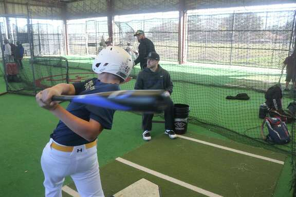 Kansas State University player Cameron Thompson tosses baseballs to campers in Deer Park's batting cage Monday. Thompson started in every Kansas State game last season, going .275 at the plate.