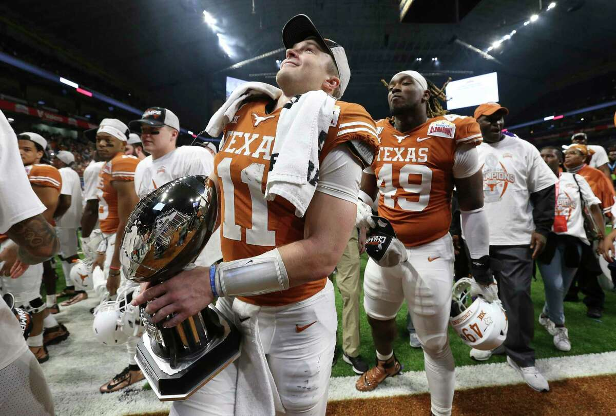 Texas Longhorns' quarterback Sam Ehlinger (11) holds the offensive player of the game trophy as the Longhorns defeated the Utah Utes at the 2019 Valero Alamo Bowl at the Alamodome on Tuesday, Dec. 31, 2019. The Longhorns defeated the Utes, 38-10, to win the 2019 Valero Alamo Bowl.