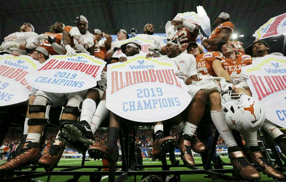 Texas Longhorn players hold Alamo Bowl signs after they defeat the Utah Utes at the 2019 Valero Alamo Bowl at the Alamodome on Tuesday, Dec. 31, 2019. The Longhorns defeated the Utes, 38-10, to win the 2019 Valero Alamo Bowl. Photo: Kin Man Hui, San Antonio Express-News / Staff Photographer / **MANDATORY CREDIT FOR PHOTOGRAPHER AND SAN ANTONIO EXPRESS-NEWS/NO SALES/MAGS OUT/ TV OUT