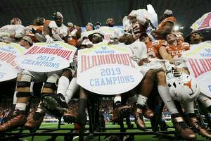 Texas Longhorn players hold Alamo Bowl signs after they defeat the Utah Utes at the 2019 Valero Alamo Bowl at the Alamodome on Tuesday, Dec. 31, 2019. The Longhorns defeated the Utes, 38-10, to win the 2019 Valero Alamo Bowl.
