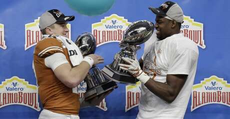 Texas quarterback Sam Ehlinger, left, and linebacker Joseph Ossai, right, celebrate the team's win over Utah in the Alamo Bowl NCAA college football game in San Antonio, Tuesday, Dec. 31, 2019. Ehlinger was named offensive player of the game, and Ossai outstanding defensive player. (AP Photo/Austin Gay)