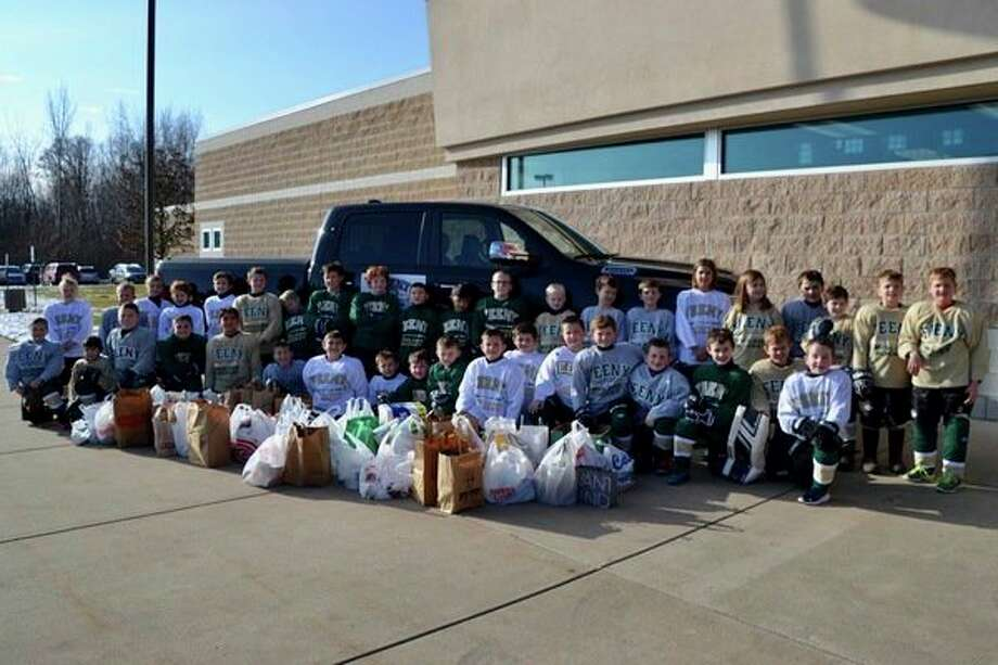 The 8U Feeny team poses with food donated during Feeny Chrysler Dodge Jeep Ram of Midland's annual holiday food drive. (Photo provided)