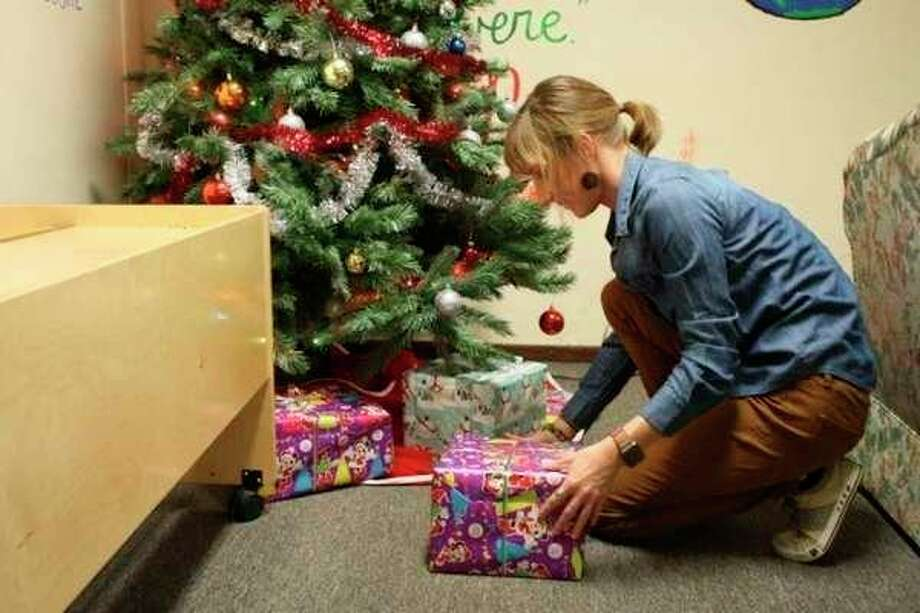 Lila Ecker, an administrative assistant at Our Brother's Keeper homeless shelter in Big Rapids, is pictured on Tuesday putting presents under a Christmas tree at the shelter. The facility is open from Nov. 1 through May 1 each year, and has the capacity to house up to 35 individuals. (Herald review photo/Time Rath)