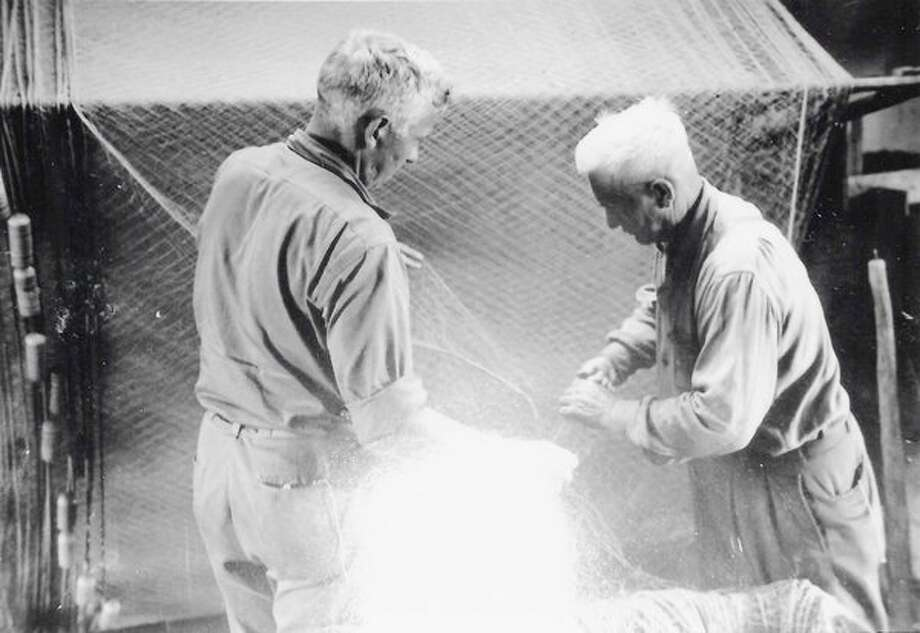 Bud and Ole Olsen mending gill nets. The Olsen fish dock wasthe last in Frankfort, razed in 1974. (Courtesy photo/ Benzie AreaHistorical Museum)