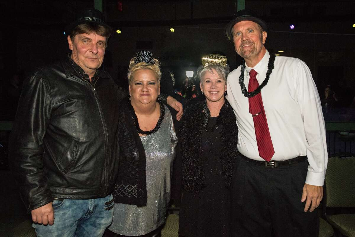 """Steve and Valarie Bauer of Davison pose with Carrie Mellican of Midland and John Walker of Marshall Midnight on Main at Dow Diamond in Midland on Tuesday, Dec. 31. The Bauers were also celebrating their third anniversary, and always come to ring in the new year together in Midland. """"This is our thing, every year,"""" Valarie said. (Danielle McGrew Tenbusch/for the Daily News)"""