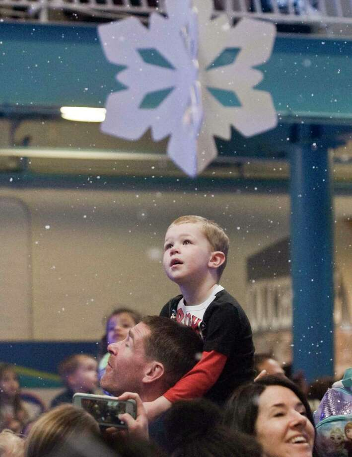 """Peter Dey, of Wilton, and his son Charles, 4, watch the artificial snow fall at the Maritime Aquarium's """"Noon"""" Year's Eve party on Tuesday. Photo: Scott Mullin / For Hearst Connecticut Media / The News-Times Freelance"""