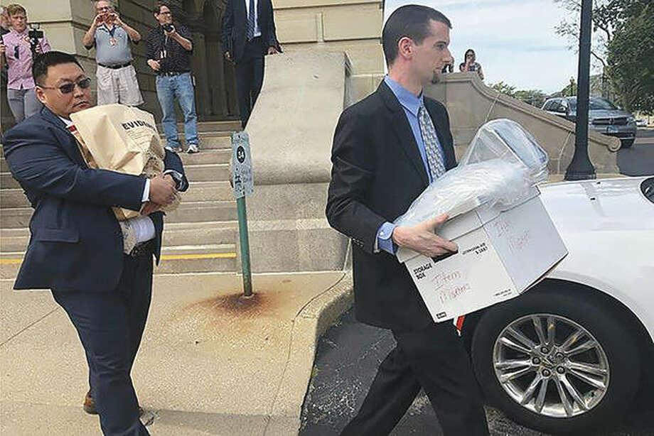 "Men carrying boxes and a bag marked ""evidence"" leave the Capitol in Springfield in September. Photo: John O'Connor 