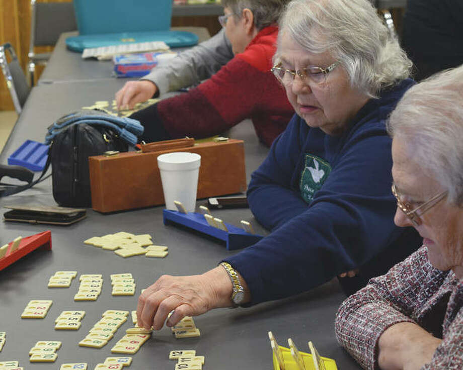 Norma Hudson of Jacksonville places a domino in a game Tuesday during the Jacksonville Senior Center's early new year party.