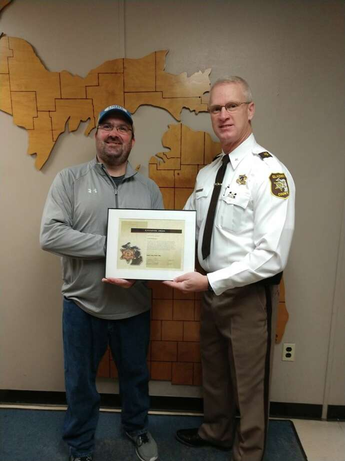 Scott McFarland, left, receives the Gladwin County Sheriff's Office Life Saving Award on Monday from Gladwin County Sheriff Mike Shea. McFarland saved two boys from a burning van on Dec. 13, following a single vehicle crash that killed two adults. (Photo provided/Gladwin County Sheriff's Office) Photo: Photo Provided/Gladwin County Sheriff's Office