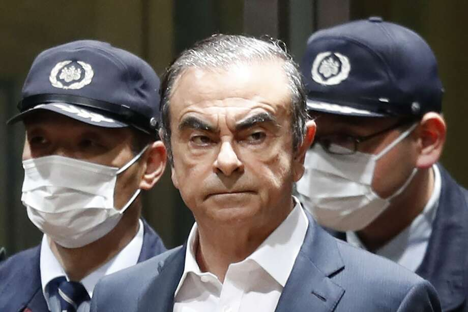 Police accompany former Nissan CEO Carlos Ghosn to a bail hearing in Tokyo in April. Photo: Associated Press 2019