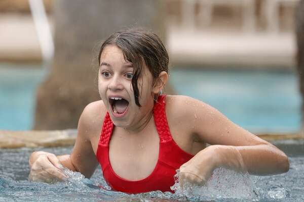 Olivia Theis reacts as she wades through 40-degree water while taking part in the Polar Bear Plunge at The Woodlands Resort, Wednesday, Jan. 1, 2020, in The Woodlands.