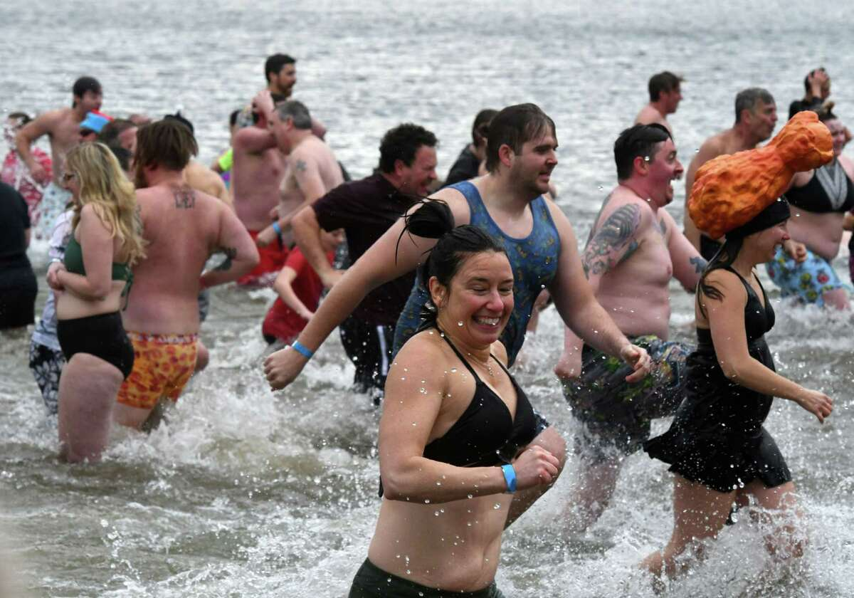 Swimmers make a hasty retreat to the shore after taking a thrilling New Year's Day dip in the icy waters of Lake George during the annual Polar Plunge event on Wednesday, Jan. 1, 2020, at Shepard Park Beach in Lake George, N.Y. (Will Waldron/Times Union)