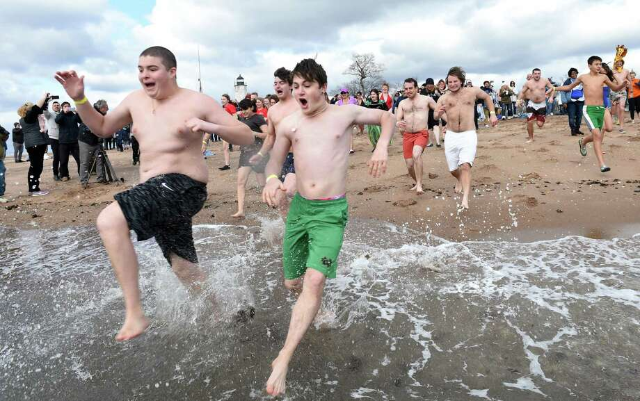 Participants in the annual Plunge for the Parks sponsored by the Elm City Parks Conservancy run into the Long Island Sound at Lighthouse Point Park in New Haven on New Year's Day January 1, 2020. Photo: Arnold Gold, Hearst Connecticut Media / New Haven Register