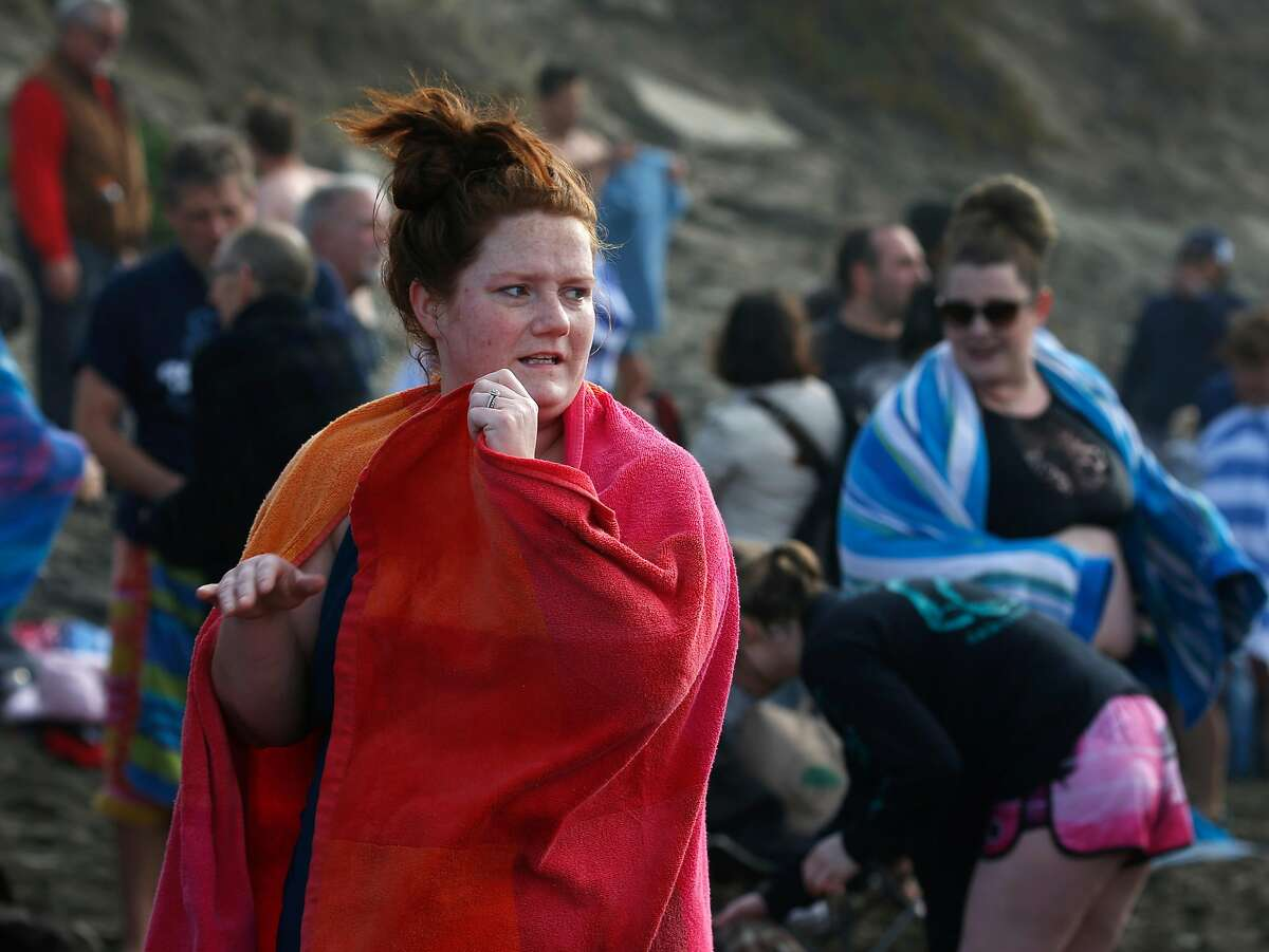Kait Lewis, is wrapped in a towel to keep warm after running into the ocean for the annual New Years Day polar plunge at Ocean Beach in San Francisco, Calif. on Wednesday, Jan. 1, 2020. Lewis came to the Bay Area from Nebraska to participate in her first polar bear plunge in the Pacific Ocean.