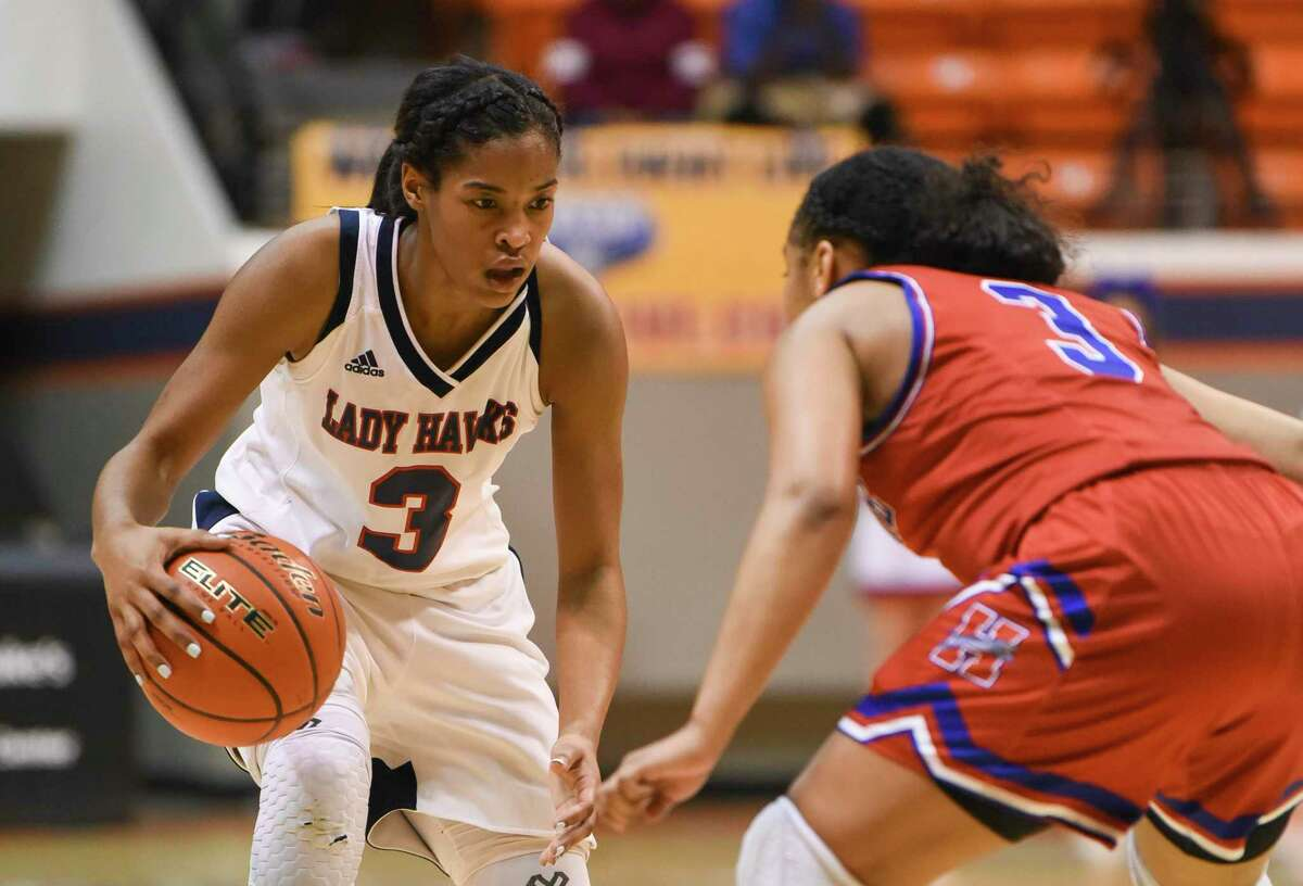 Hardin-Jefferson's Ashlon Jackson tries to get around Midlothian-Heritage's Jasmine Bailey during the first half of the regional semi-finals playoff game at Sam Houston State University on Friday. Photo taken on Friday, 02/22/19. Ryan Welch/The Enterprise