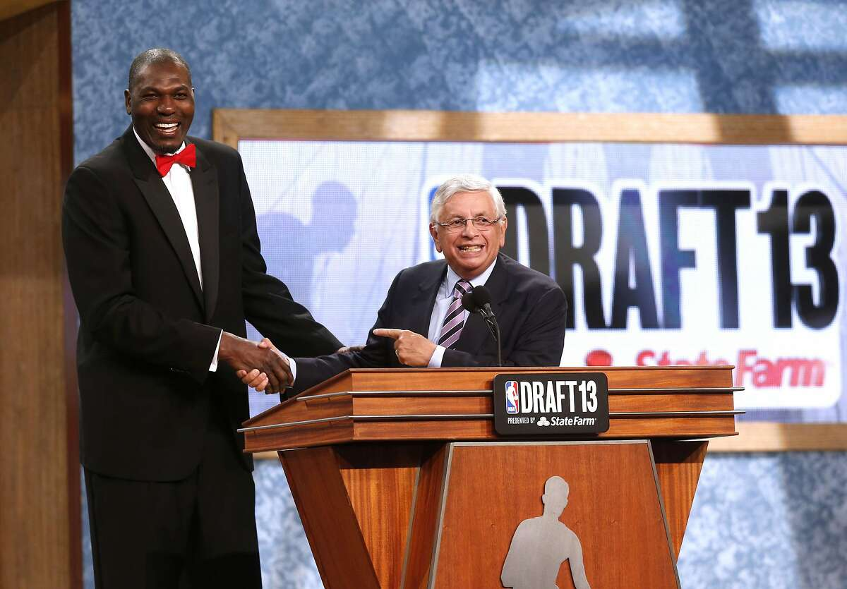 Retired NBA star Hakeem Olajuwan, left, shakes hands with NBA Commissioner David Stern after coming onstage to pay tribute to Stern at the end of the first round of the NBA basketball draft, Thursday, June 27, 2013, in New York. Stern is retiring in February. (AP Photo/Jason DeCrow)