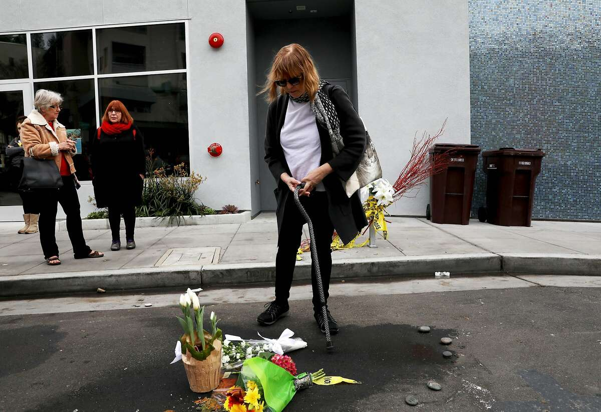 Sharon Silberman looks at a memorial after leaving flowers at the scene where a man was critically injured on New Year's Eve outside of a Starbucks, located at 2080 Mountain Blvd., in Montclair, Calif., on Wednesday, January 1, 2020. The man chased the thief out to the getaway car and was critically injured trying to thwart the theft of his laptop and later died of injuries he suffered as a result. On New Year's Day the Oakland Police Department announced two men had been arrested in connection with the incident.