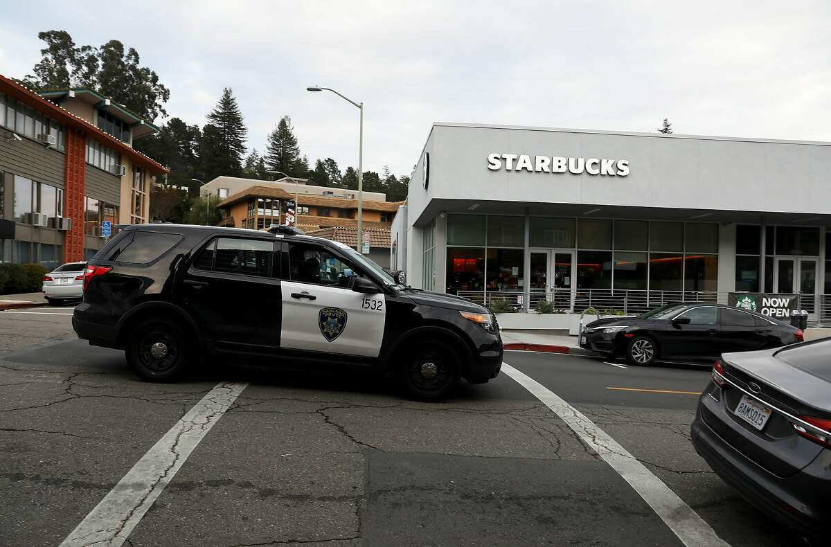An Oakland police vehicle passes by the Starbucks where a worker's laptop was stolen last New Year's Eve. The man chased the thief, but was fatally injured trying to stop him.