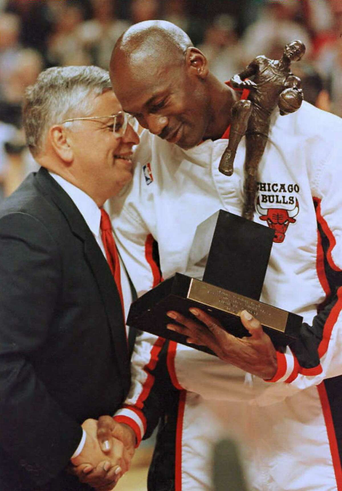 (FILES) In this file photo taken on May 21, 1996 National Basketball Association (NBA) Commisioner David Stern (L) congratulates Chicago Bulls guard Michael Jordan during the 1996 NBA Most Valuable Player trophy presentation. - Magic Johnson and Michael Jordan were among the NBA legends stunned by the death on January 1, 2020 of former league commissioner David Stern following a brain hemorrhage he suffered last month. Stern, who was 77, spent 30 years as commissioner before retiring in 2014 and oversaw the NBA's growth from a league whose finals weren't televised live to a global sport empire with a worldwide following and talent. (Photo by BRIAN BAHR / AFP) (Photo by BRIAN BAHR/AFP via Getty Images)