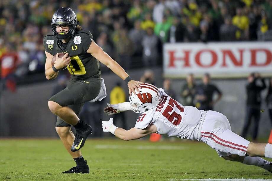 Oregon's Justin Herbert eludes Wisconsin's Jack Sanborn on his go-ahead TD run in the fourth quarter. Photo: Mark J. Terrill / Associated Press