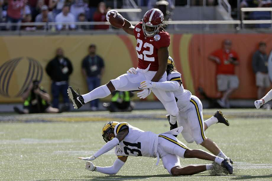 Alabama running back Najee Harris (22) gains yardage as he tries to get past Michigan defensive back Vincent Gray (31) and defensive back DeMarcco Hellams, right, during the first half of the Citrus Bowl NCAA college football game, Wednesday, Jan. 1, 2020, in Orlando, Fla. (AP Photo/John Raoux) Photo: John Raoux / Associated Press