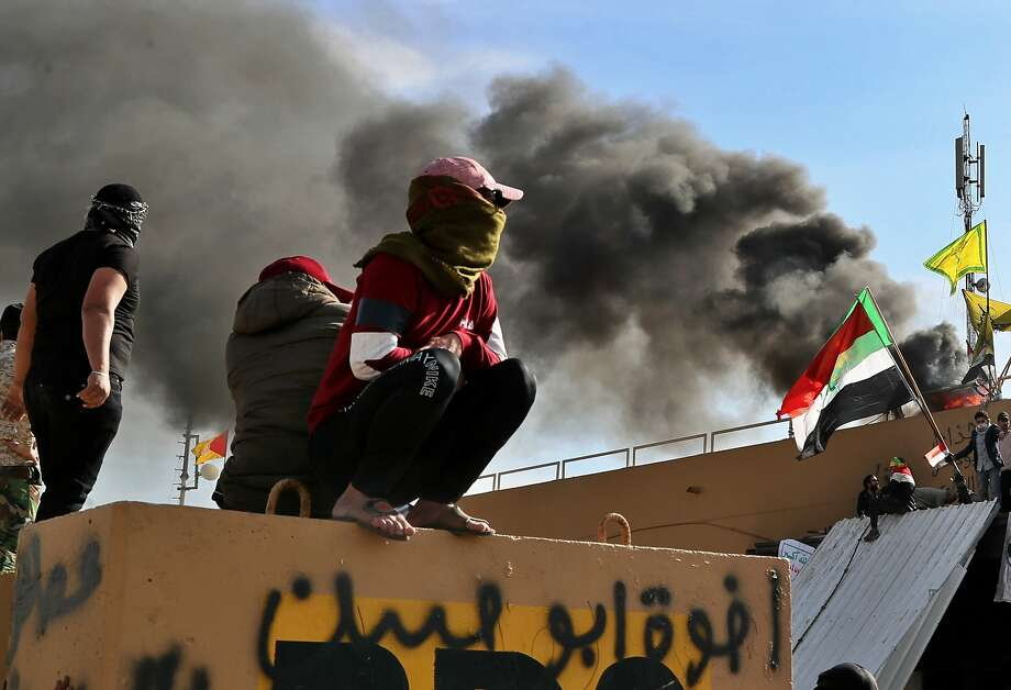 Pro-Iranian militiamen and their supporters set a fire during a sit-in in front of the U.S. embassy in Baghdad, Iraq, Wednesday, Jan. 1, 2020. U.S. troops have fired tear gas to disperse hundreds of pro-Iran militiamen and other protesters who were gathered for a second day outside the American Embassy compound in Baghdad. (AP Photo/Khalid Mohammed) Photo: Khalid Mohammed, Associated Press