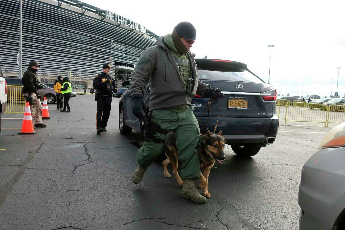 A law enforcement with a dog inspects vehicles parking at MetLife Stadium, Wednesday, Jan. 1, 2020, in East Rutherford, N.J., at an event called Siyum HaShas, that celebrates the completion of the reading of the Babylonian Talmud, a process that takes 7-1/2 years The large gathering of Jews drew a significant security presence after recent anti-Semitic attacks in the New York City area. (AP Photo/Ted Shaffrey)