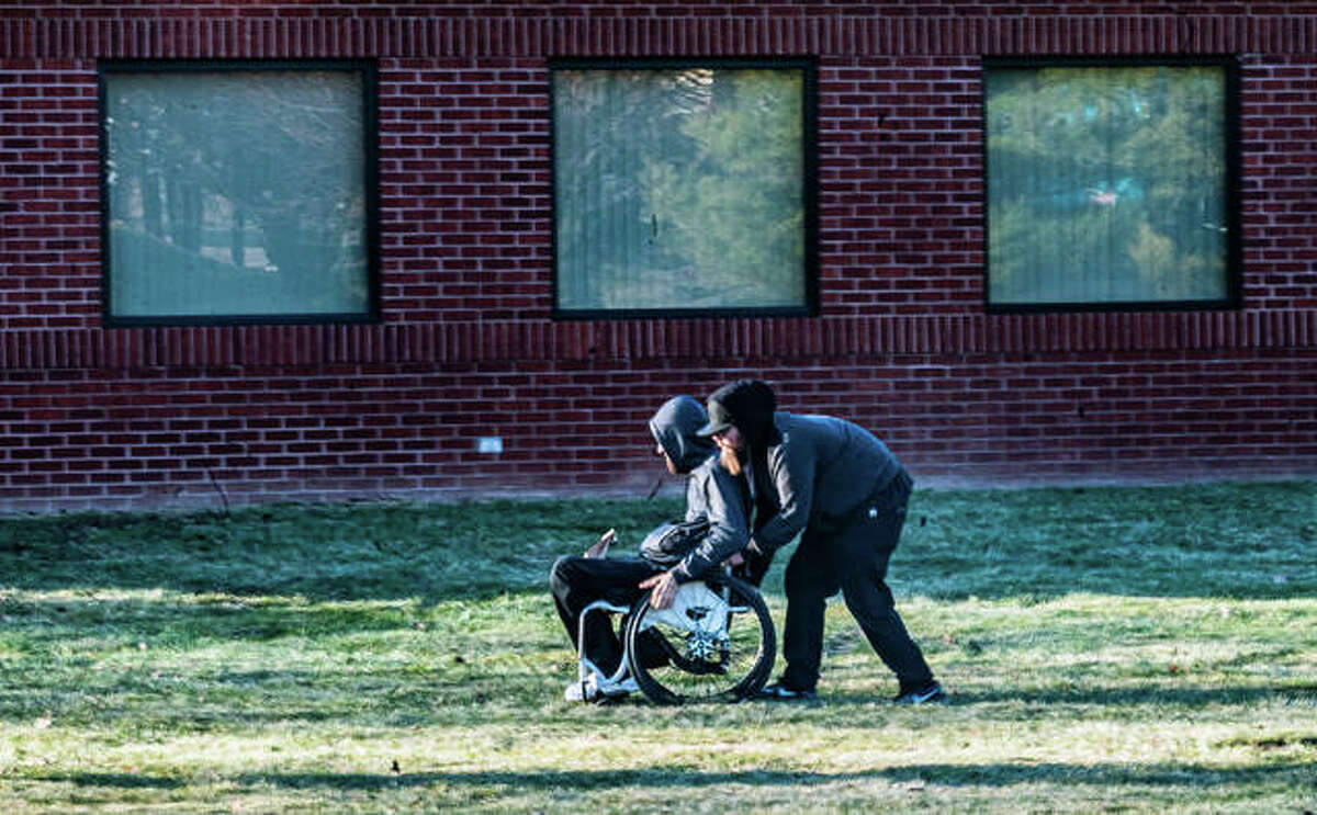 A man assists an elderly man in a wheelchair, a Wednesday purchase resting on his lap, across a lawn adjacent to HCI Alternatives in Collinsville.