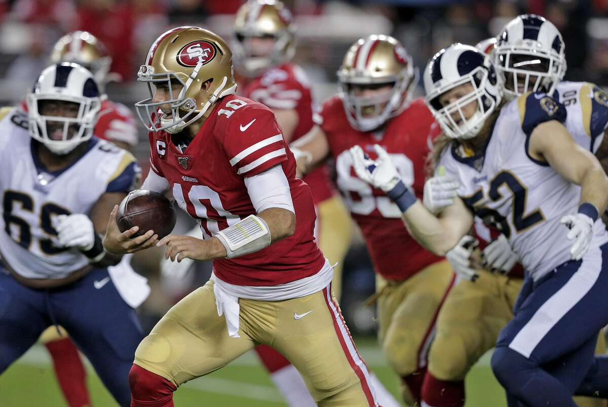 Jimmy Garoppolo (10) scrambles for a first down in the fourth quarter as the San Francisco 49ers played the Los Angeles Rams at Levi's Stadium in Santa Clara, Calif., on Saturday, December 21, 2019.