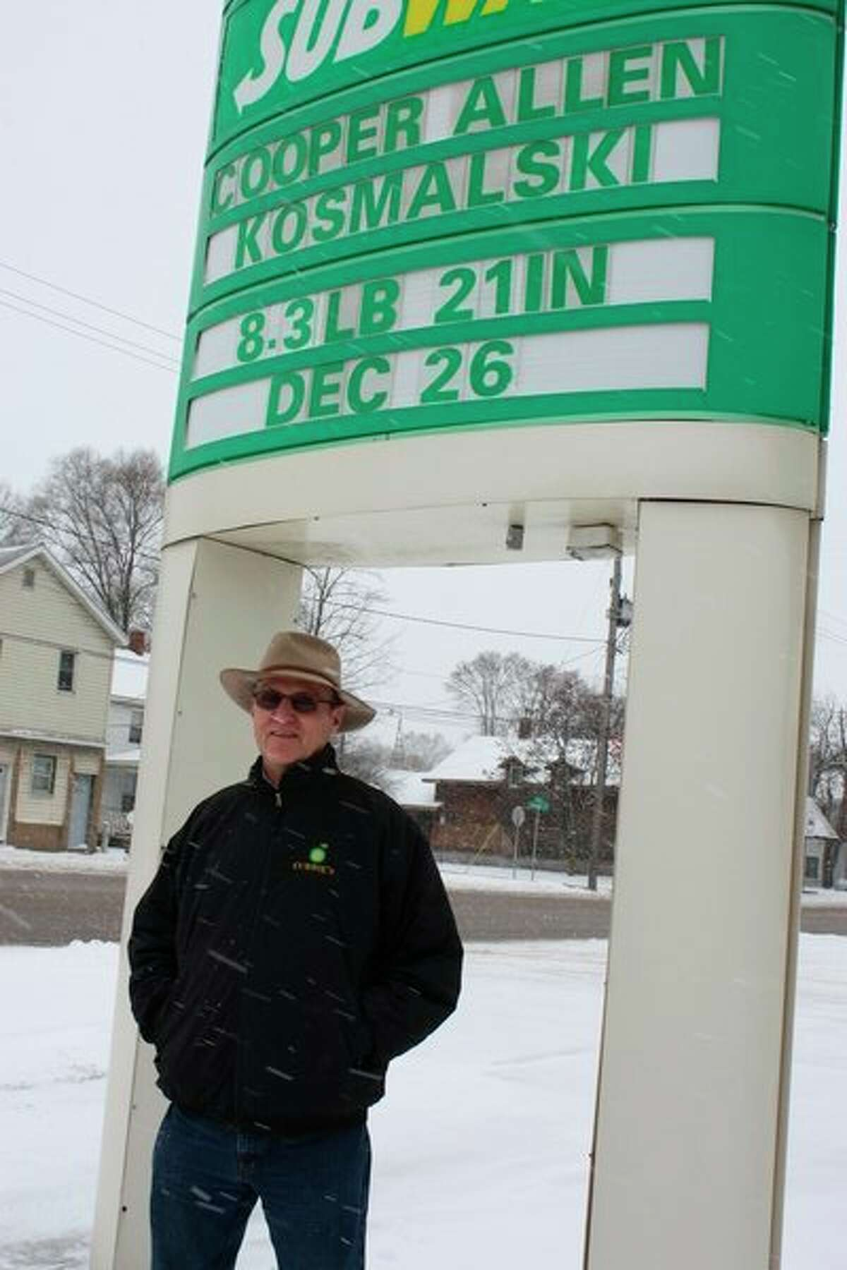 Pat Currie stands underneath the marquee of the BP gas station he owns, 620 Maple St., in Big Rapids. For more than 20 years, Currie has used the marquee to inform drivers and passersby of local news, such as births, deaths, anniversaries and more. (Pioneer photo/Tim Rath)